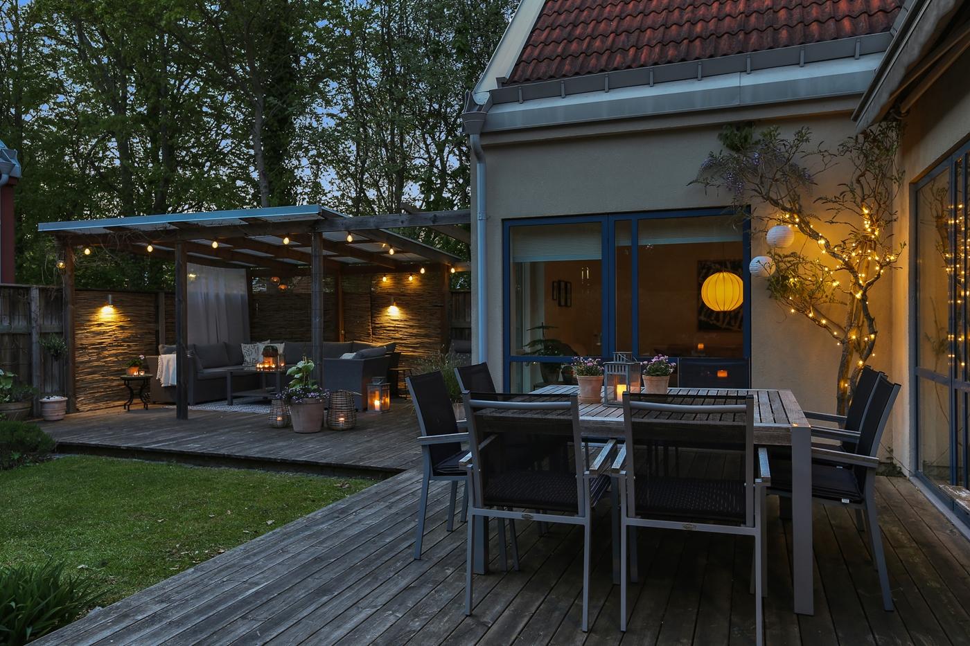 Trädäck med plats för stor matplats och loungedel med pergola samt skärmtak.