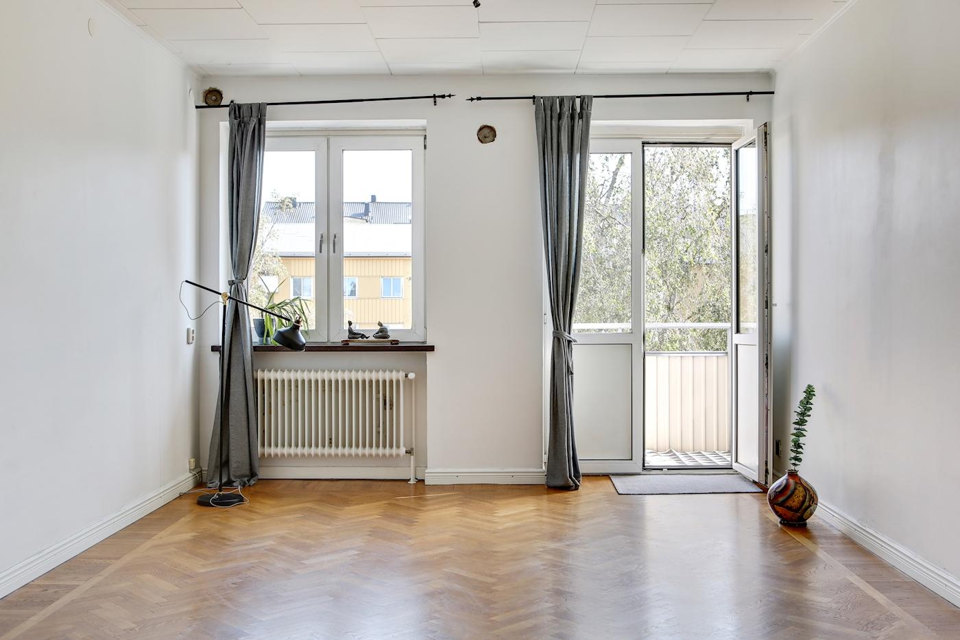 Ljust vardagsrum med utgång till balkong.