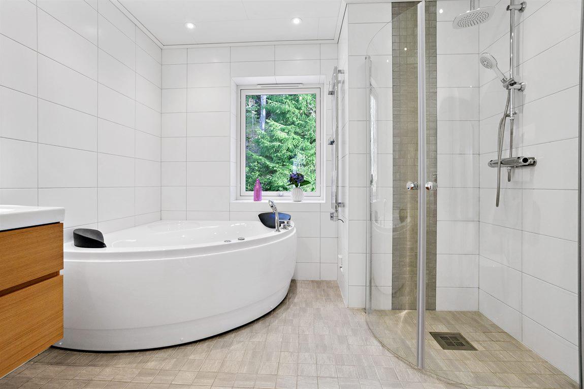 Stort och stilrent badrum på övre plan