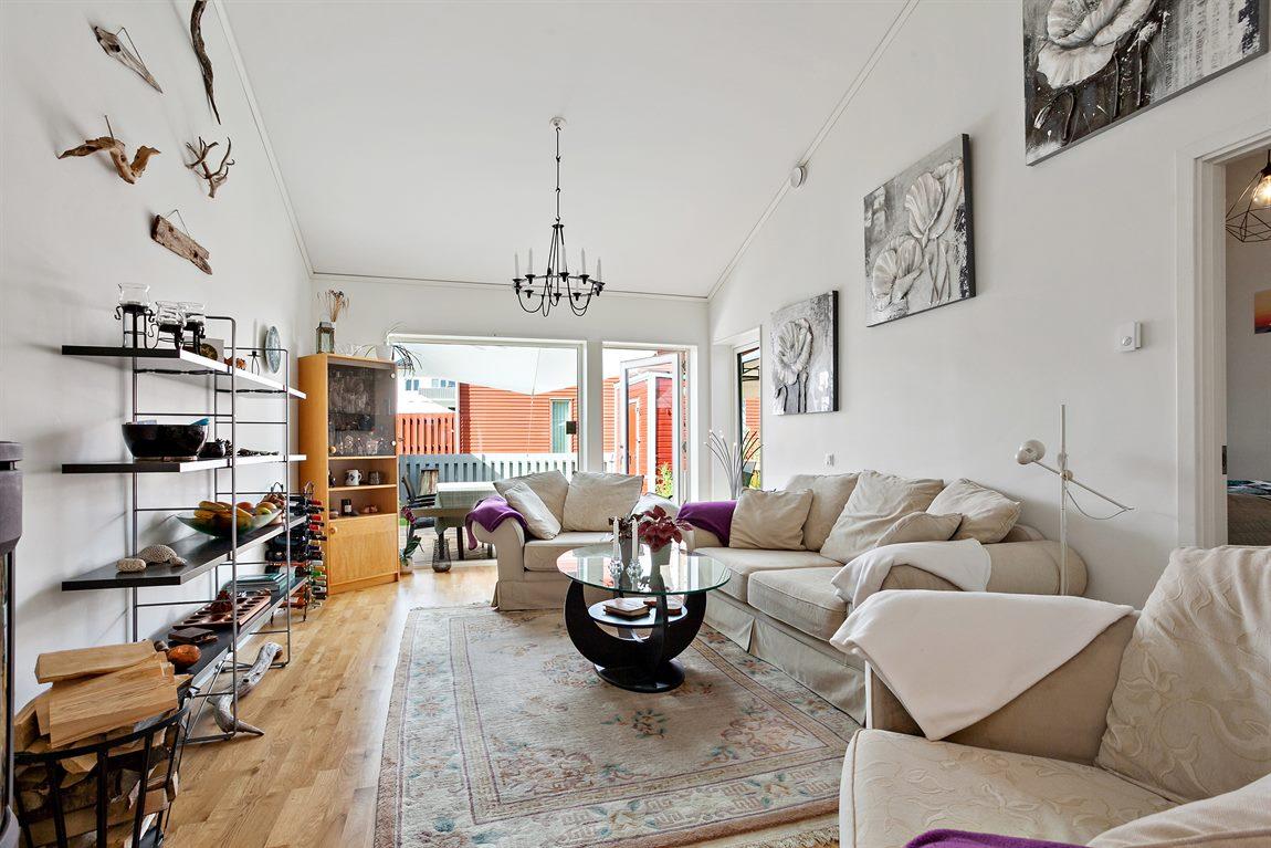 Generöst vardagsrum med fint ljusflöde och utgång till altan