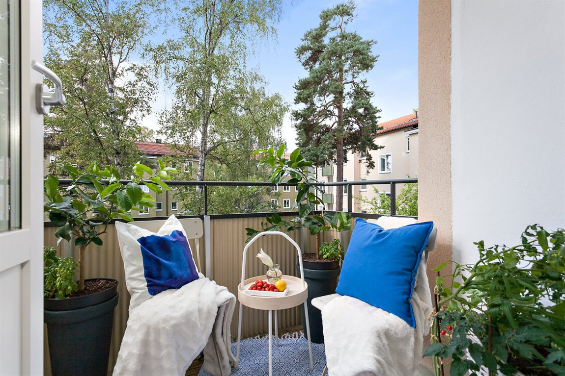 Trivsam balkong med utsikt mot den trevliga innergården