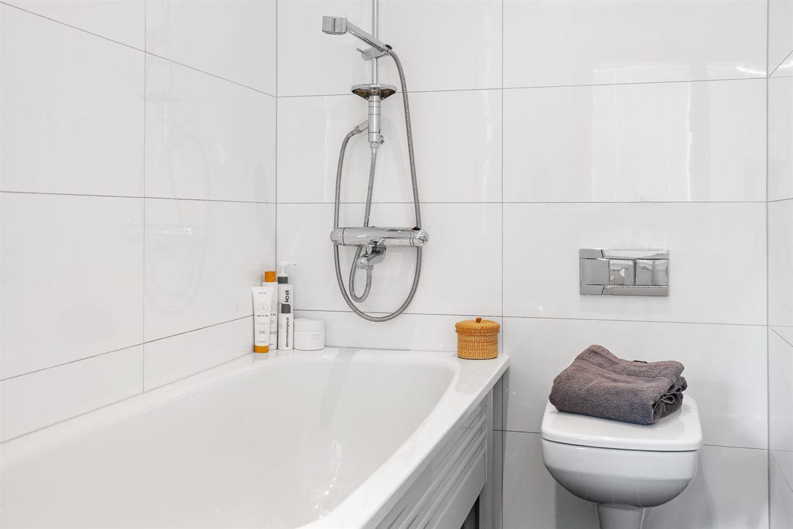 Badkar med takdusch och vägghängd WC
